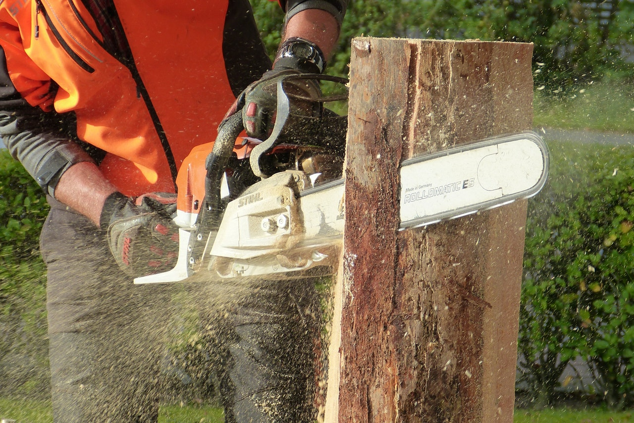 Man in orange safety vest chainsawing a tree trunk vertically