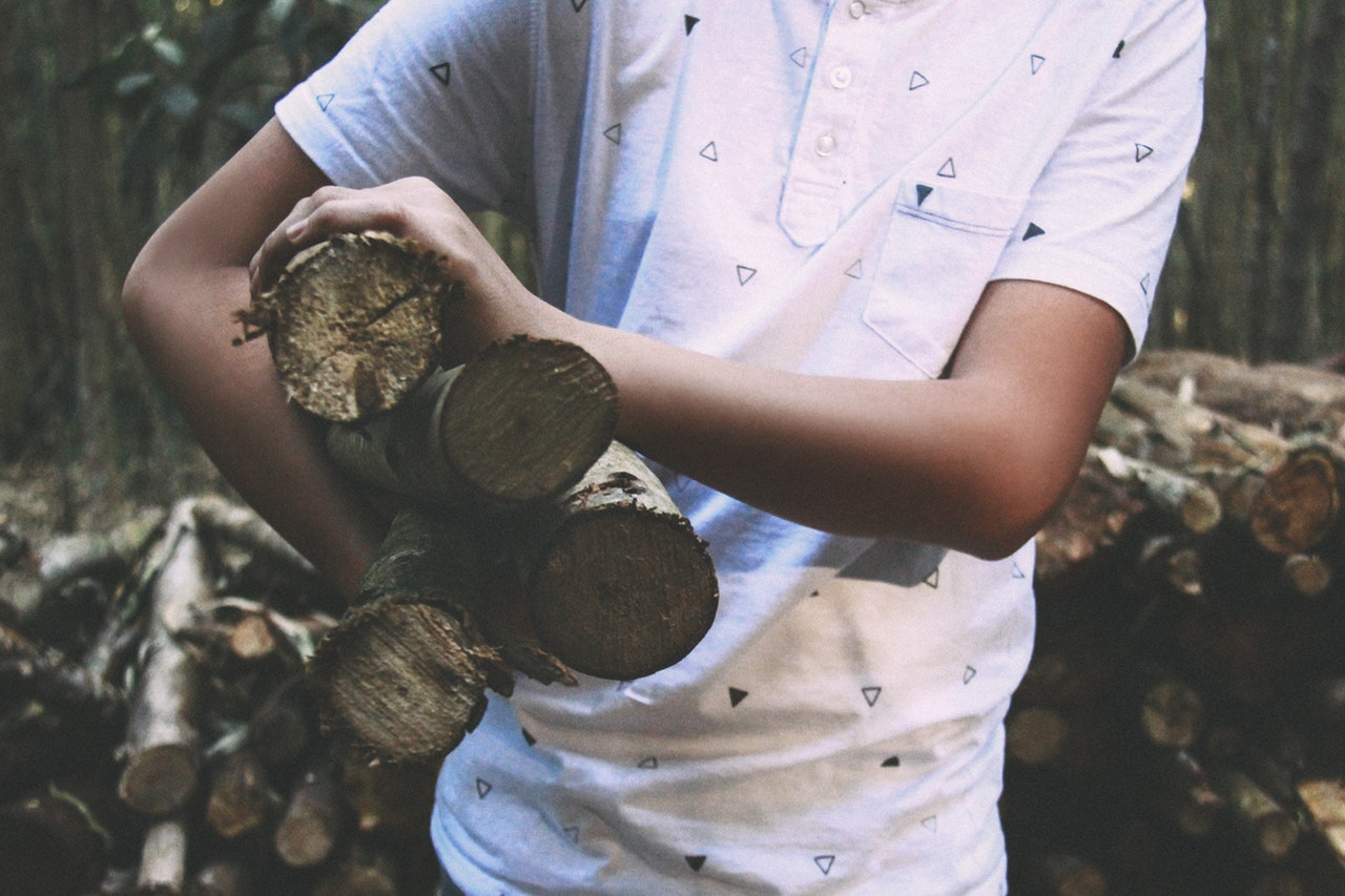 Man in patterned white shirt holding four logs under his right arm